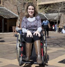 Young woman in wheelchair in university courtyard