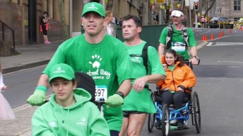 Marthon runners pushing wheelchair at Blackmores Running Festival 2014