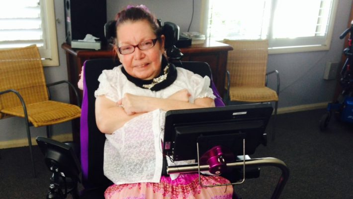 woman in her 50s with cerebral palsy in a wheelchair with mounted communication device