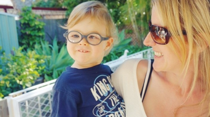 Little boy with glasses looking at camera while being held by mum who is looking at him