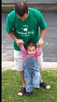 Little Sarah being helped by her dad to walk through the gates of her preschool