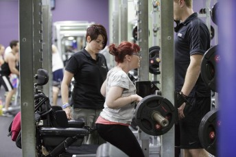 Girl standing in front of her wheelchair and lifting weights while being supervised by exercise physiologist