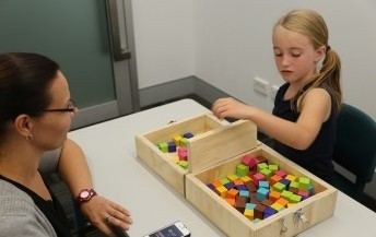 girl with cerebral palsy playing with blocks as part of an assessment