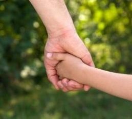 adult's hand grasping a child's hand