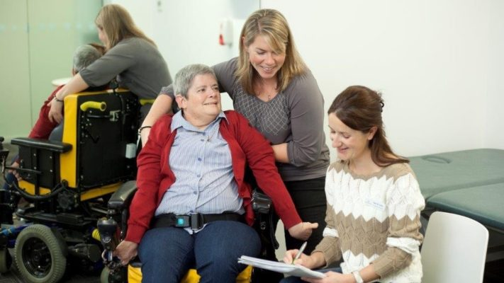 woman in wheelchair being attended to by two therapists - one standing behind her and one sitting in front of her taking notes