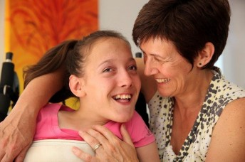 young girl with cerebral palsy in a wheelchair being hugged by her mum