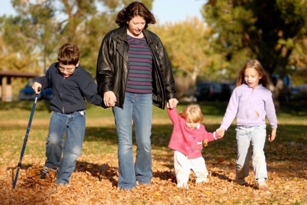 group photo of family walking through a park - includes young boy with walking stick holding hand of woman who is holding the hand of a toddler