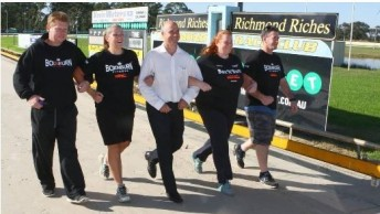 5 adults in sports outfits linking arms walking together