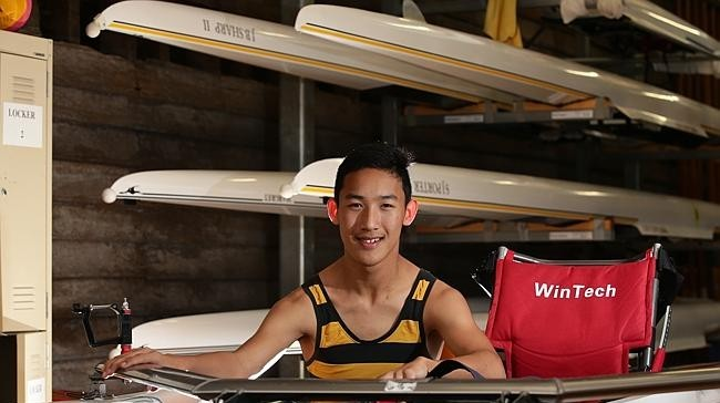 Boy wearing black and yellow singlet sitting in front of stack of rowing boats
