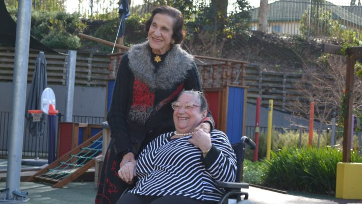 Dame Marie Bashir standing next to and holding the hand of her female cousin sitting in a wheelchair