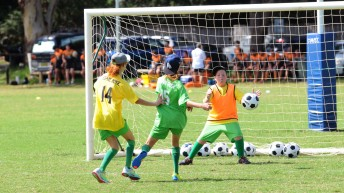 2 girl soccer players kicking ball into a soccer net defended by young male goalkeeper