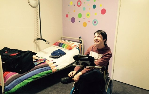 young man in a wheelchair in a room at a respite centre - bed, hoist and colourful wall in background