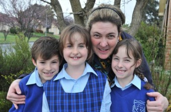 2 girls and 1 boy in school uniform with mum crouching behind them