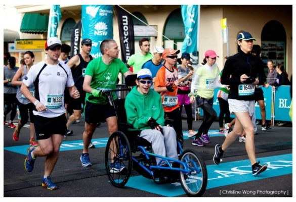 Man in wheelchair being pushed by able-bodied man in Blackmores Running Festival (Sydney)