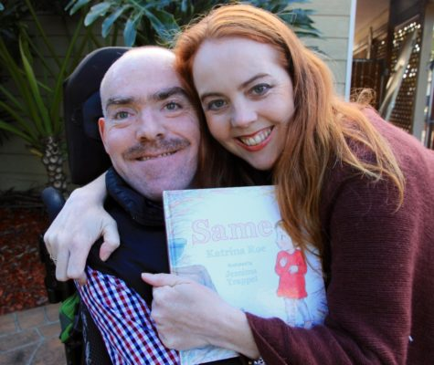 adult brother and sister Charlie and Katrina smiling at camera and holding the book 'same' authored by Katrina