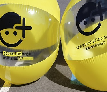 two inflatable beach balls with social inc logo