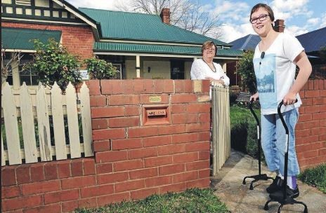 Young woman (with walking sticks) standing outside her front fence with her mother in the background
