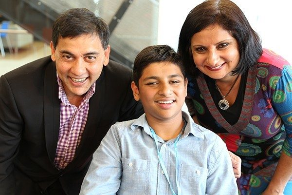 Indian teenager sitting between his mum and dad