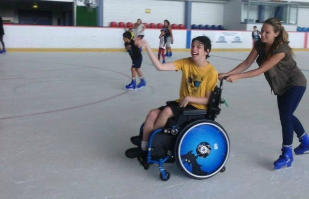 young man in a wheelchair ice skating - he is being pushed by his carer on an ice rink