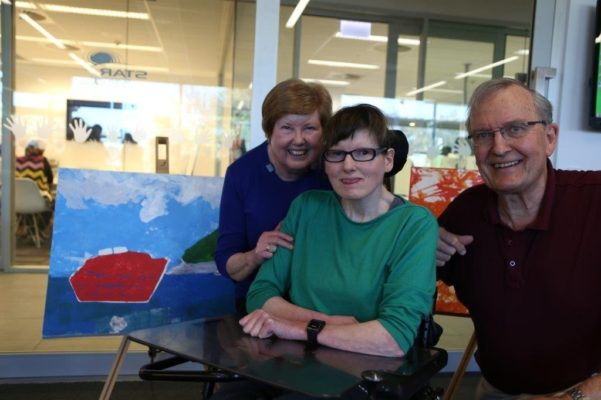 woman in wheelchair with her parents and her artwork on display