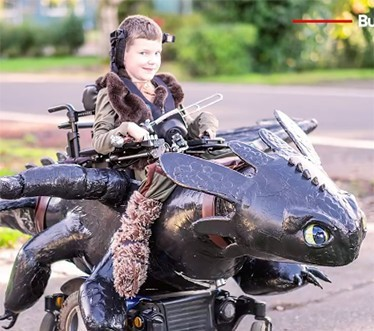 Young boy in a wheelchair that has been turned into a Halloween costume of How to Train a Dragon character, Toothless