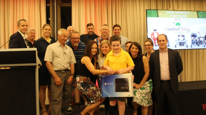Nine year old Alex holding playstation surrounded by Westfield Golf Day participants and supporters