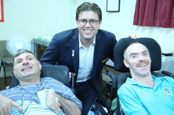 Ryde Mayor Jerome Laxale crouching beneath 2 men sitting in wheelchairs - all smiling at the camera