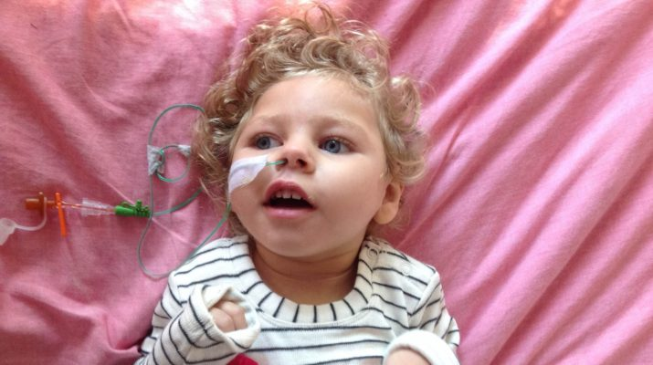 Little girl Indigo who has cerebral palsy laying on a pink blanket smiling