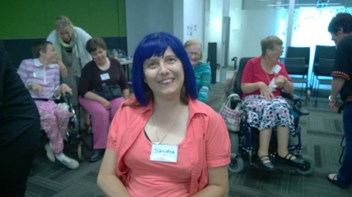 Sandra who has CP wearing a purple wig at a women's pampering day at Allambie Campus