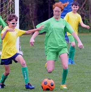 boy and girl with cerebral palsy kicking soccer ball with boy in the background