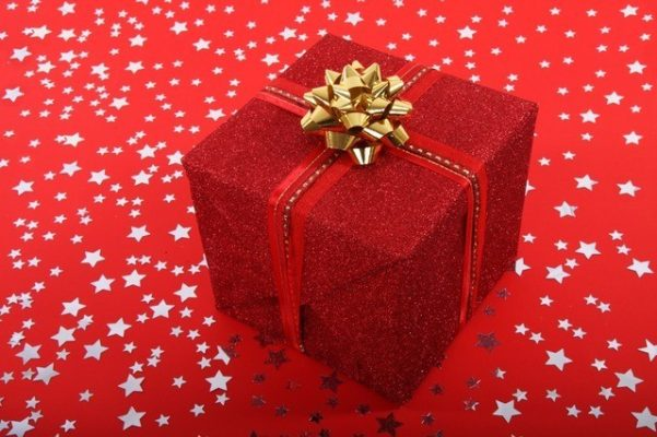 Christmas gift box wrapped in red paper with red ribbon and gold bow on red background with silver stars