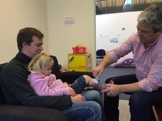girl sitting on her father's lap while have her calf measured for orthotics by specialist