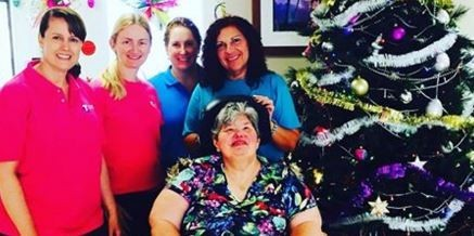 4 women standing behind a lady in a wheelchair - all next to a Christmas tree