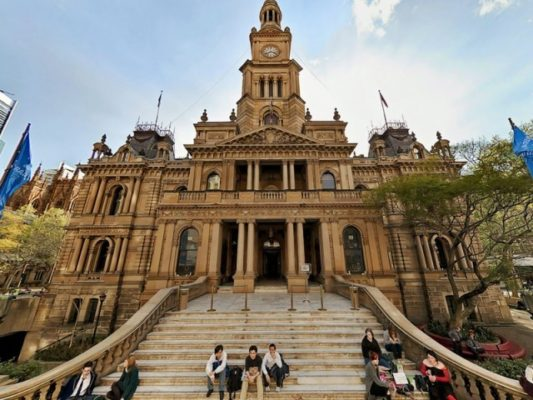 Sydney Townhall with small groups of people sitting on the front steps