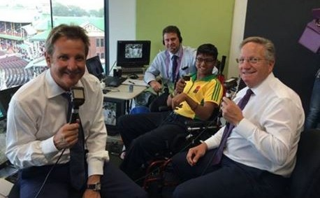 boy with cerebral palsy wearing yellow cricket shirt sitting in a wheelchair with the Channel Nine TV cricket commentary team