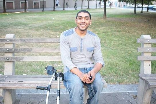 Young man sitting on a park bench next to his crutches and smiling at the camera