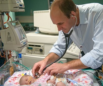 Doctor checking a baby in NICU with a stethascope