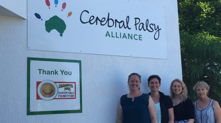 The entrance to Cerebral Palsy Alliance Port Macquarie office with signage thanking Sargents Pies Charitable Foundation for their support and four of the staff