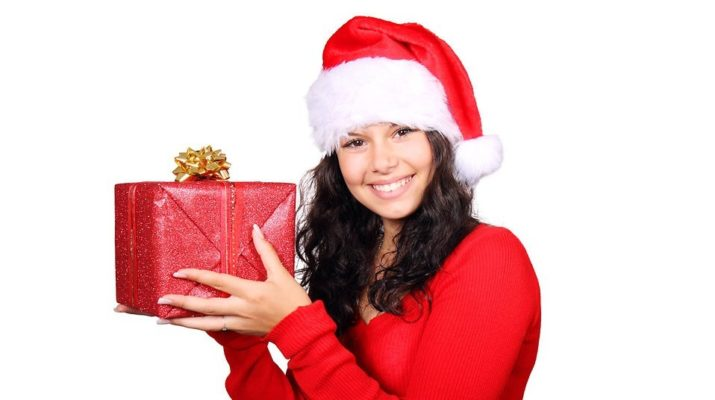 A woman in Santa hat holding up a beautifully wrapped present.
