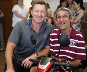 Man with cerebral palsy sitting in scooter sitting next to man crouching beside him - both smiling to camera