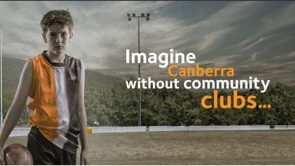 Advertising image of child on football field holding a ball and dressed in football uniform with catch phrase Imagine Canberra without community clubs