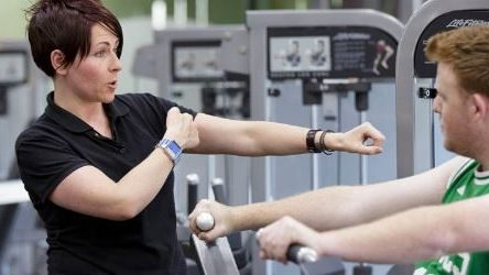 An Exercise Physiologist with a person working out in the gym
