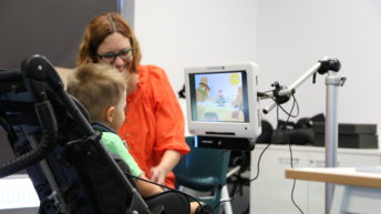 Child in wheelchair using eye gaze technology with a therapist