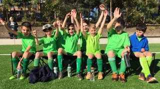 Eight young boys with cerebral palsy sitting on a bench cheering.