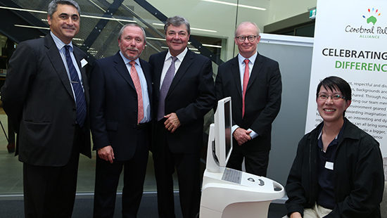 four men in suits standing next to man who is sitting in front of a 3D scanning dentistry machine
