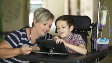 Mother sitting with her son who is in a wheelchair as they look at his ipad.