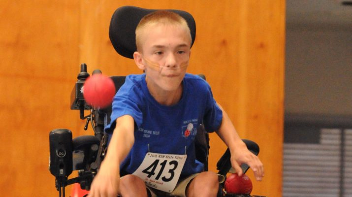 Young boy in wheelchair playing boccia