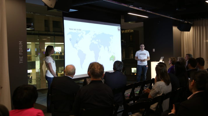 Abilio founders Jessica and Steve King are presenting their investment pitch to a crowd. On the screen used for their presentation is a world map.