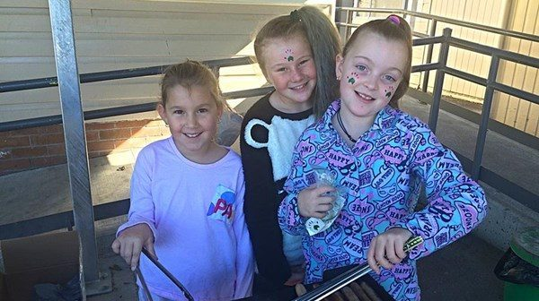 three young girls smiling at the camera with fake tatoos of Cerebral Palsy Alliance's logo on their faces