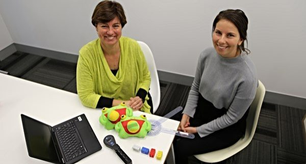 Two female cerebral palsy researchers sitting at table with laptop and toys looking up at camera and smiling